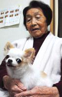 膝の上に乗るリリーを「家族」と語る西沢さん