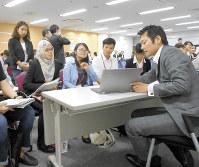 企業の担当者(右)から説明を聞く留学生=京都市下京区のナジック学生情報センターで