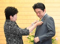 Tokyo Gov. Yuriko Koike, left, puts a Tokyo Olympics and Paralympics badge on Prime Minister Shinzo Abe before their meeting, at the prime minister's office on Jan. 10, 2017. (Mainichi)
