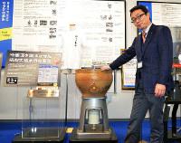 吟醸酒を誕生させた研削式精米機の説明をする宗貞健広報室長=東広島市西条西本町のサタケ本社で、信永真知子撮影