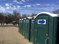 A row of portable restrooms, with the name