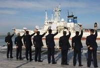制帽を振って巡視船えりもを見送る釧路海上保安部の幹部ら=北海道釧路市で15日