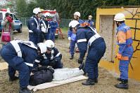 倒壊家屋から負傷者役を救出する警察官や消防団員=奈良県五條市で、栗栖健撮影