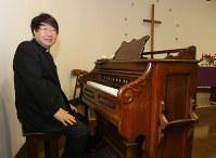 今も現役で使われている「西川オルガン」の前に座る米澤講治牧師=銚子市西小川町の日本キリスト教団銚子教会で