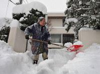 雪かき作業は重労働。準備運動などをして、けがや心臓発作を防ごう=札幌市豊平区で2016年12月10日、手塚耕一郎撮影
