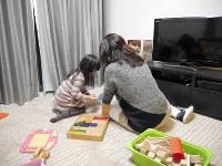 家事の合間に長女と遊ぶ女性。「夫の長時間労働がなくならない限り、妻の負担は減らないと思う」という==東京都内で、中村かさね撮影