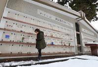 カトリック高田教会の集合墓で、姉・中島邦さんの墓碑を見つめる笹川芳さん=新潟県上越市で、小川昌宏撮影