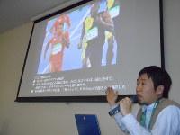並走するケンブリッジ飛鳥選手にウサイン・ボルト選手が思わず見入る瞬間を撮影した写真について説明する梅村記者=横浜市中区で