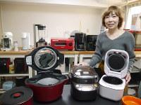 家電アトリエで調理家電を紹介する神原さん。右から、生ものでも予約調理が可能なシャープの無水調理鍋「ヘルシオホットクック」、圧力調理ができる象印の「煮込み自慢」、ごはんとおかずが同時調理できるタイガーの炊飯器「tacook」=東京都渋谷区で