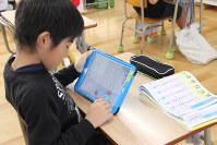 漢字を部品に分解し、書き順通りに自動的に書き上がるプログラムを書く。最後の花丸も自動でつけていた=大分県臼杵市立福良ケ丘小学校で2016年12月12日、岡礼子撮影