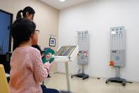 治療用眼鏡で視力を測る子供=東京都中央区の日本橋はま眼科クリニックで