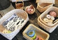 ふだん使いの小物も、かごに収めれば雰囲気のあるインテリアに。魚柄の布巾が入った左端から時計回りに▽秋田・イタヤカエデ▽ラトビア・シラカバ▽ラトビア・柳▽長野・マタタビ▽長野・マタタビ▽岩手・スズタケ=東京都国立市西2のかご専門店「カゴアミドリ」で