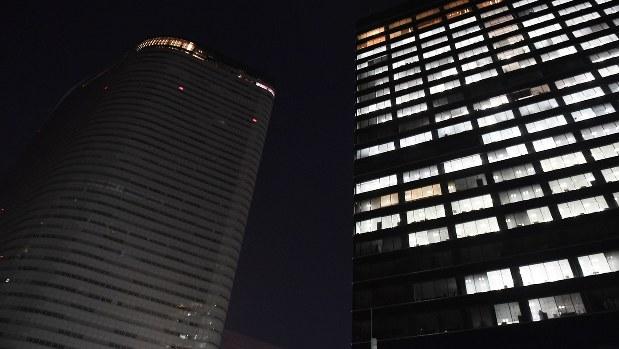長時間労働による社員の自殺を受け、午後10時に一斉消灯されるようになった電通の本社ビル(左)=2016年10月24日、猪飼健史撮影