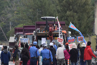 Protesters stand in the path of vehicles involved in offshore work in the Henoko district of Nago, Okinawa Prefecture, and chant a slogan in front of the U.S. military's Camp Schwab in Nago on Feb. 6, 2017. (Mainichi)