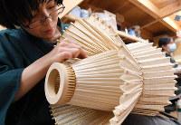 折り目を確認しながら和風照明を仕上げていく松本光彩さん=京都市上京区の「京和傘 日吉屋」で、小松雄介撮影
