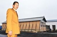 修復された有形文化財「客車庫」(中央の建物)前で、くりはら田園鉄道の制服姿で立つくりでん保存愛好会の鎌田健会長=宮城県栗原市で
