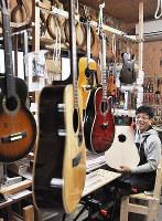 「とんでもなく壊れたギターを持ち込まれるとわくわくする」と語る山本和哉さん=和歌山市で、成田有佳撮影