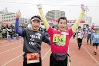 2015年大会で盲人フルマラソンの部に出場した松本康治さん(右)とともにゴールした三菱商事の村上啓二さん=同社提供