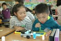 プログラミングの授業で、タブレットで車型ロボットを動かす児童=佐賀県武雄市の市立山内西小で2016年11月、林由紀子撮影