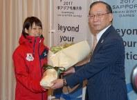 選手村の開村セレモニーで花束を受け取る高木菜那選手(左)=帯広市で