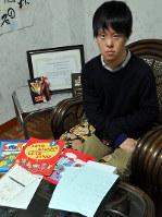 勉強した英語のテキストや賞状などを前に語る中西健志さん=和歌山市で、成田有佳撮影