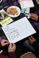 ボランティアの指導で、難民の男性(左)が書いたひらがな=大阪市淀川区で、三浦博之撮影