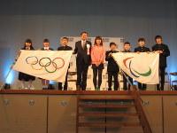 高橋さん(中央)から五輪旗を受け取った浜中市長(左から4人目)=青梅市内で