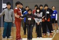 田中佑典選手(左から2人目)に前転の補助をしてもらい、笑顔を見せる女の子
