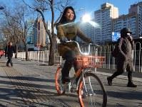 「モバイク」の自転車を利用する畢銘明さん。同社だけで北京市内に10万台を超える自転車を配置している=中国北京市で