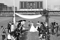 大勢の参列者に祝福される新郎新婦=東大阪市花園ラグビー場で、望月亮一撮影