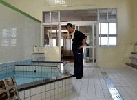 営業開始前にタイルや浴槽を確認する和泉哲さん=徳島県小松島市小松島町の日の峰温泉で、河村諒撮影