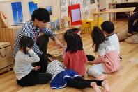 女児に囲まれて遊ぶ男性保育士=恵庭市相生町の市こすもす保育園で
