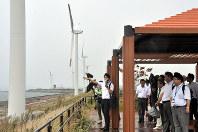 響灘地区で北九州市が昨年開いた洋上風力発電所の事業者向け現地説明会。風力発電適地のため、既に沿岸に風力発電設備が稼働している=北九州市若松区で、石田宗久撮影