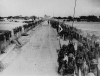 1937年7月、北京郊外の盧溝橋を渡る日本軍兵士