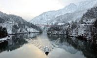 雪化粧した山々を背景に、庄川を進む遊覧船=富山県の庄川峡で、古川宗撮影