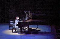 「全曲リクエスト」のコンサートで一人、ピアノを弾き語る。楽譜は使わず、歌詞カードを見るだけ。「700曲以上あるので、途中で分からなくなる曲もありますが……」=東京都渋谷区で、宮間俊樹撮影