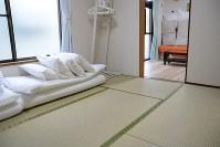 東京ディズニーランドに近い木造アパートの一室にある民泊施設。寝具が並ぶ6畳の和室のほか、洋室や台所もある=千葉県浦安市で