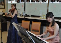 ホテルのロビーで演奏する佐藤友衣さん(右)と簗瀬彩さん=羽島市で