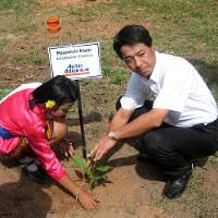2007年、タイ北部チェンマイの学校で、寄付の記念に植樹する小飼さん(右)=マツダ提供