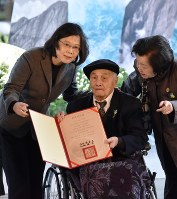 事件の被害者(中央)に名誉回復証書を手渡した蔡英文総統(左)=28日、鈴木玲子撮影