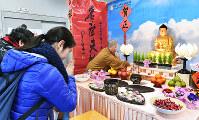 春節祭の会場に設置された佛光山寺の仏壇に手を合わせる来場者たち=大阪市浪速区の大阪中華学校で、小関勉撮影