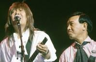 1989年(平成元年)6月10日、神奈川県横浜市の横浜アリーナで、懐かしいグループサウンズ(GS)のメンバーが集まって「タイガース・メモリアル・クラブ・バンドコンサート」が行なわれた。翌年大阪で開催される「花の万博」のいのちの塔建設運動PRのための公演で、ザ・タイガース、ザ・ワイルドワンズなどのメンバーが熱唱した。「タイガース・メモリアル・クラブ・バンドコンサート」のステージで歌う、元ザ・スパイダースのかまやつひろしさん(左)。右はザ・ワイルドワンズの加瀬邦彦さん=神奈川県横浜市の横浜アリーナで1989年(平成元年)6月10日、滝雄一撮影