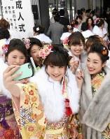 記念写真を撮る新成人たち。成人式のために住民票を移さない若者は少なくない=札幌市中央区で1月9日、竹内幹撮影