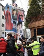 朴槿恵前大統領の私邸前に駆けつけた支持者たち。朴氏の写真入りの旗には「あなたを応援している」などと書かれている=ソウル市江南区で2017年3月12日、大貫智子撮影