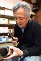 気持ちよい開け閉めのため、内筒の「キイ」を金づちでたたいて調整する=京都市下京区で、小松雄介撮影