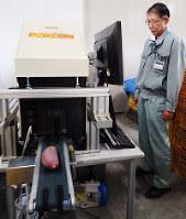 サツマイモの糖度を計測できる装置を使う徳島県立農林水産総合技術支援センターの梯美仁統括研究員=徳島県鳴門市のJA大津松茂で、同センター提供