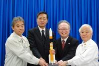 打ち上げ後の記者会見で記念撮影するJAXAの奥村理事長(右端)ら