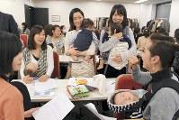 乳児を抱えて職場復帰セミナーに参加する女性たち=東京都新宿区で