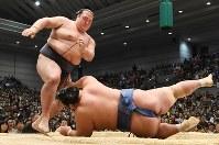 稀勢の里(左)が突き落としで琴奨菊を降す=エディオンアリーナ大阪で2017年3月20日、小松雄介撮影