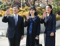 Princess Aiko, center, waves to well-wishers ahead of her graduation ceremony at Gakushuin Girls' Junior High School, flanked by Crown Prince Naruhito and Crown Princess Masako, in front of the Toyama Campus of Gakushuin schools in Tokyo's Shinjuku Ward on March 22, 2017. (Pool photo)